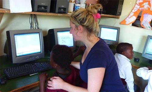 A Kaya volunteer teaching children how to use a computer