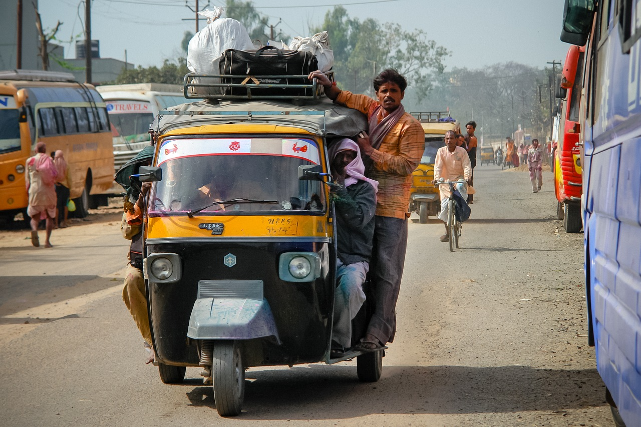 Man on a rickshaw on a busy steet in India