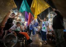 A procession of dancers with and without disabilities, with flags including a wheelchair user at the L'Arche London 40th birthday.