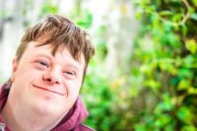 A man with Downs Syndrome in a garden,smiles for the camera.