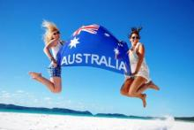Girls jumping on the beach with an Australia flag