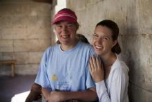 Two women, one with with learning disabilities smile for the camera in a shady stone building.
