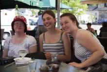 Three women, including one with Downs Syndrome sit at a cafe table.